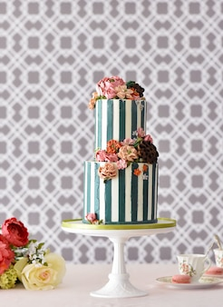 Two-tiered delicious cake with the decoration of colorful flowers on a white stand