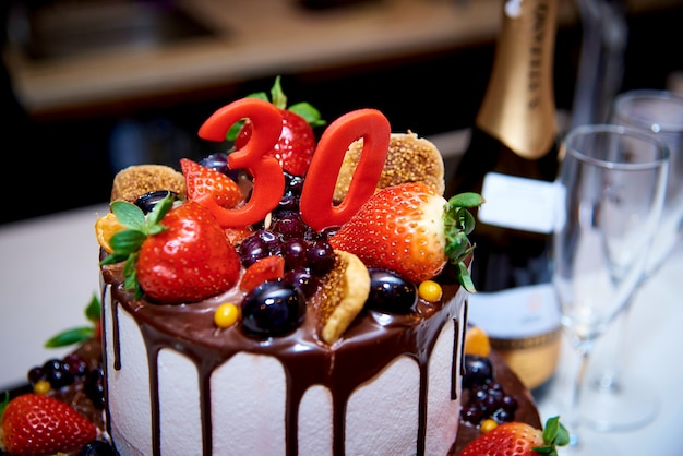 A two-tiered white cake with fresh fruit and chocolate stands next to a bottle of champagne