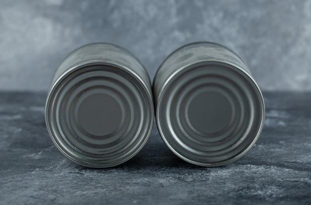 Two tin cans placed on marble.