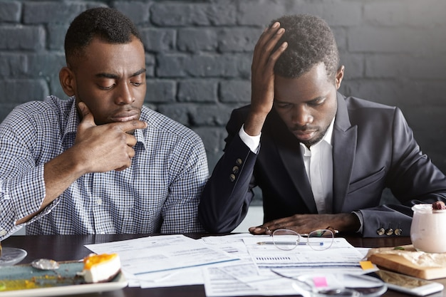 書類をやっている2人の疲れて落ち込んでいるアフリカ系アメリカ人のビジネスマン