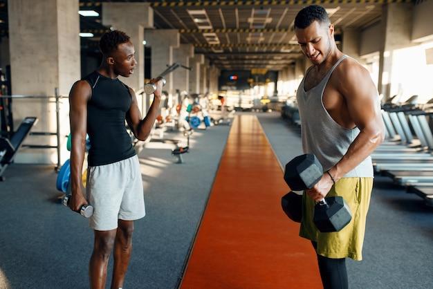 Два усталых спортсмена делают упражнения с гантелями, тренируются в тренажерном зале