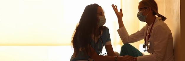 병원 복도에서 의료 마스크를 쓴 두 명의 피곤한 의사