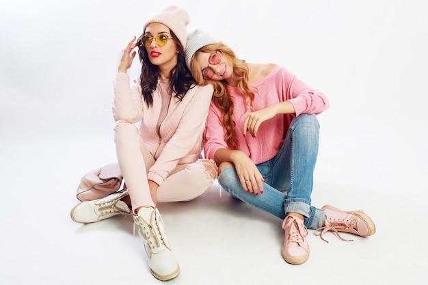 Due amici stanchi che si rilassano sul pavimento bianco in studio. vestito rosa carino. scarpe alla moda.