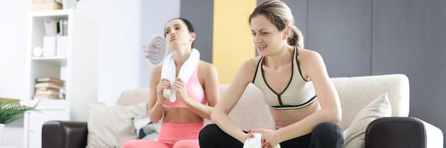 フィットネストレーニングホームトレーニングとトレーニングプログラムの後、2人の疲れた女性がソファに座っています