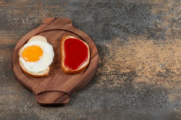 目玉焼きとジャムを木の板に載せたトーストパン2枚。