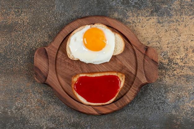 나무 접시에 튀긴 계란과 잼 두 토스트 빵.