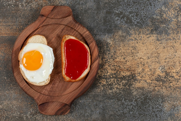 Two toast bread with fried egg and jam on wooden plate.