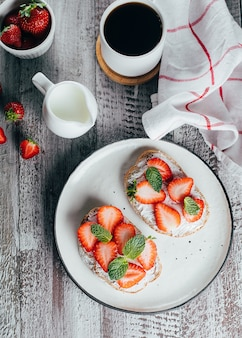 Two toasts or bruschetta on plate with strawberry on cream-cheese and cup of coffee on wooden table