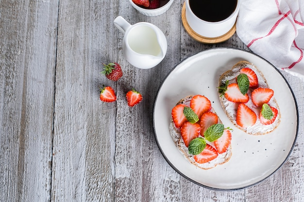 Two toasts or bruschetta with strawberry and mint on cream-cheese and cup of coffee on wooden table