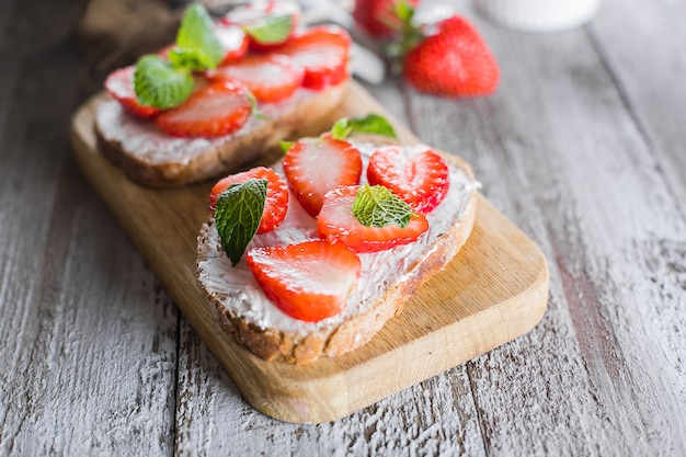 Two toasts or bruschetta with strawberry and mint on cream-cheese on wooden board on table