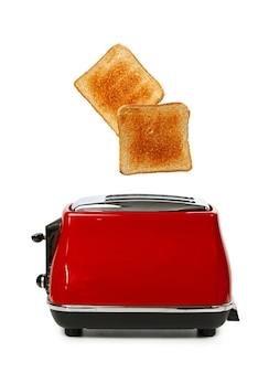 白に対して赤い電気トースターから飛び出す2つのトースト