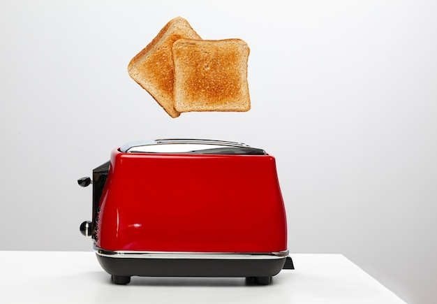 Two toasts jumping out of red electric toaster on white