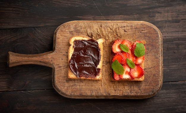 Two toasts with chocolate paste and fresh ripe red strawberries on a brown wooden board