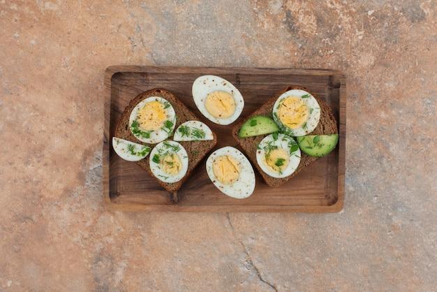 Два тоста с огурцом и вареными яйцами на мраморном столе.