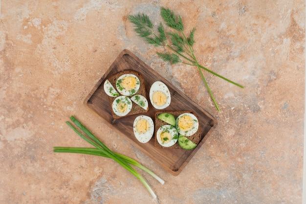 대리석 테이블에 오이와 삶은 달걀을 넣은 토스트 2 개.