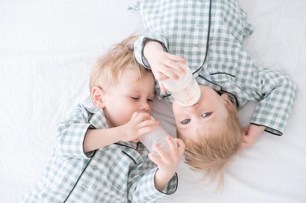 Двое малышей-близнецов в пижамах лежат на кровати и пьют молоко из бутылочек. откровенная домашняя детская жизнь.