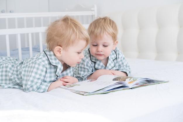 Два мальчика-близнеца малыша в пижаме читают книгу лежа