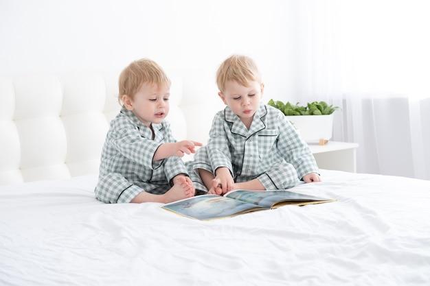 Двое малышей-близнецов в пижамах читают книгу, сидя на белых постельных принадлежностях на кровати