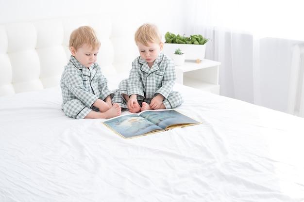 Два мальчика-близнеца малыша в пижамах, читая книгу, сидя на белых постельных принадлежностях на кровати.