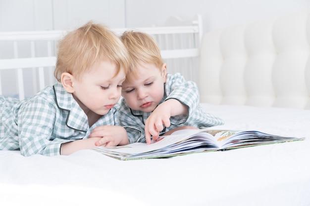 Двое маленьких мальчиков-близнецов в пижаме читают книгу