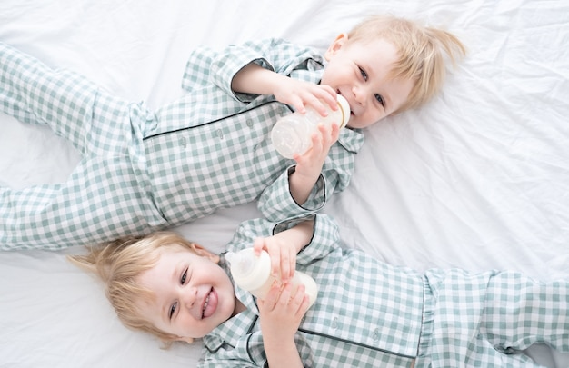 Two toddler baby twin boys in pajamas lie on bed drinking milk from bottles