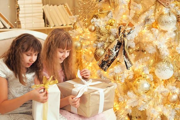 クリスマスプレゼントを開く豪華な白いクリスマスツリーの近くの2人の幼児の女の子。