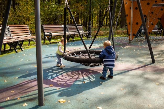 소년과 소녀 두 명의 유아가 놀이터의 그네 해먹에서 즐겁게 놀고 그네를 타다