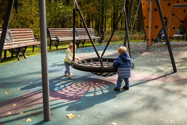 Two toddlers a boy and a girl play cheerfully and swing on a swing hammock on a playground in the