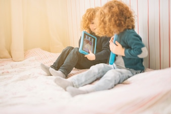 Two toddlers sitting on bed playing with digital tablet
