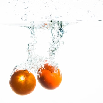 Two tomato falling into the water over white background