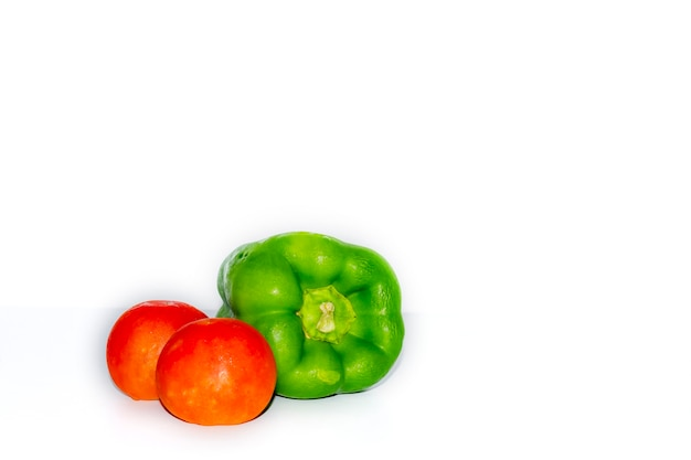 Two tomatoes and a capsicum green chili isolated on white background, healthy vegetables concept photography