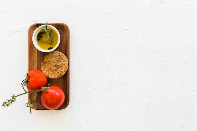 Two tomatoes with bread and black pepper oil on wooden tray