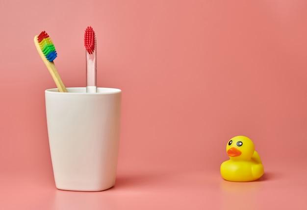 歯ブラシとアヒルのおもちゃ2つ、コピースペース。口腔を保護し、歯垢と歯石を取り除くためのパーソナルケアツール。