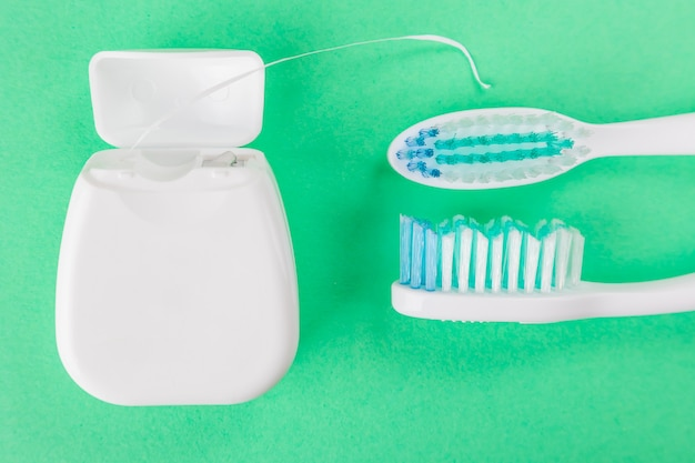Two toothbrushes and dental floss on a green background