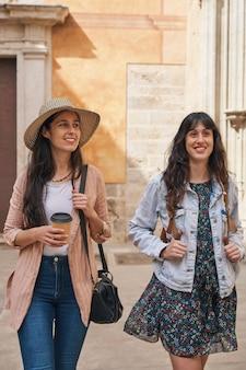 휴가에 도시 거리를 걷는 두 명의 관광 소녀