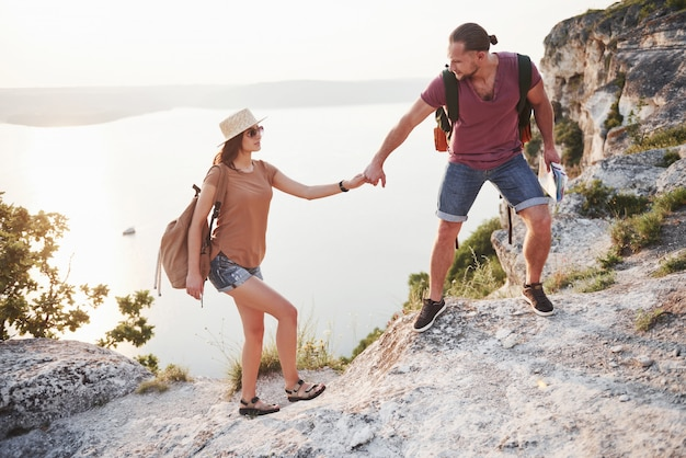 2つの観光客の男性とバックパックを持つ女性は山の頂上に登り、日の出を楽しんでいます。旅行ライフスタイル冒険休暇コンセプト