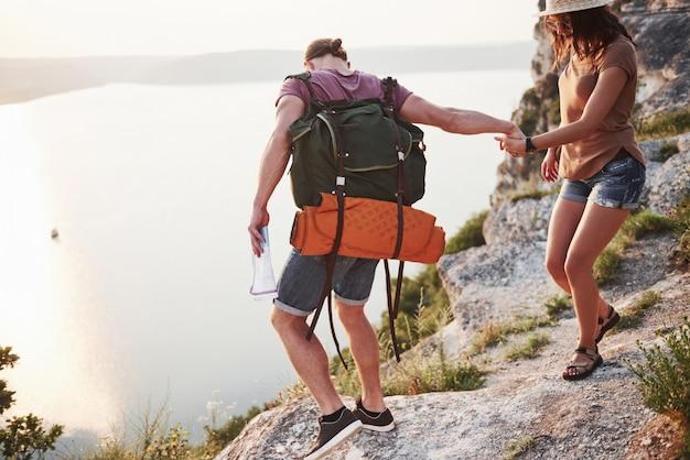 배낭과 두 관광 남자와 여자는 산의 정상에 올라 일출을 즐기는.