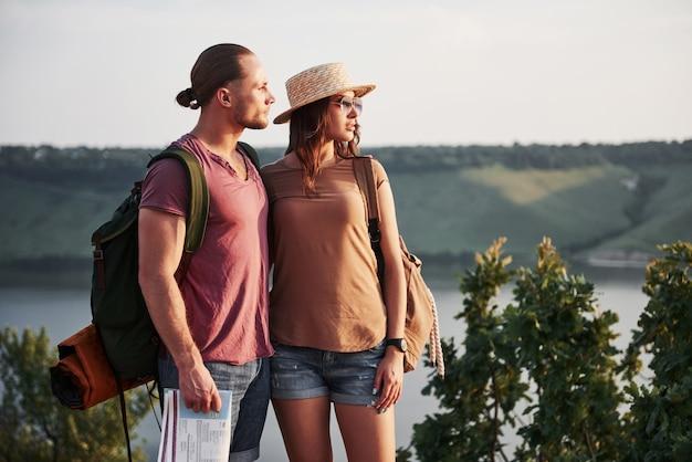 2つの観光客の男性とバックパックを持つ女性が岩山の頂上に立ち、日の出を楽しんでいます。山と海岸の旅、自由とアクティブなライフスタイルのコンセプト