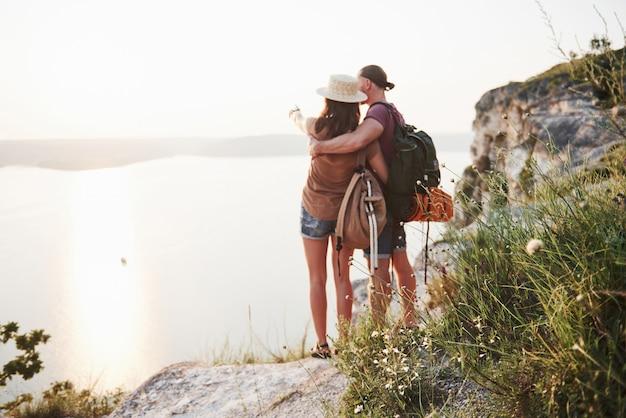 2つの観光客の男性とバックパックを持つ女性が岩山の頂上に立ち、日の出を楽しんでいます。