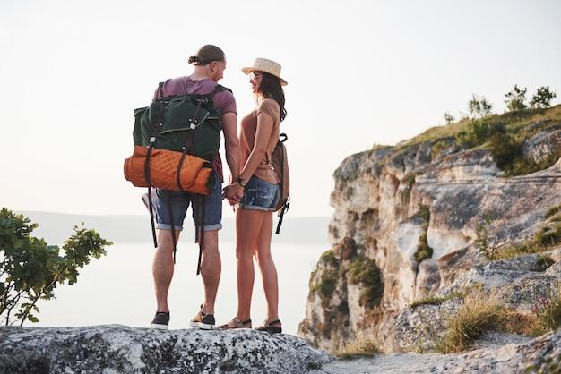 2つの観光客の男性とバックパックを持つ女性が山の頂上に立って、日の出を楽しんでいます。旅行ライフスタイル冒険休暇コンセプト