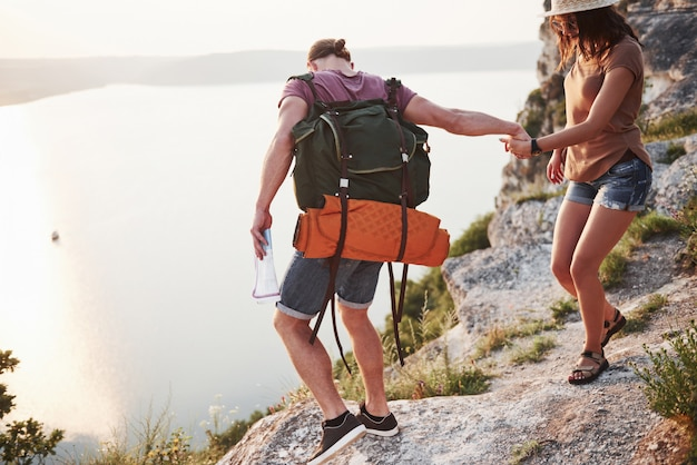 Two tourist male and woman with backpacks climb to the top of the mountain and enjoying sunrise.