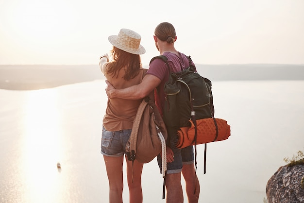 Two tourist male and woman with backpacks stand to the top of the mountain and enjoying sunrise.