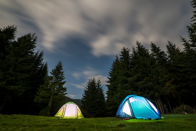 Two tourist tents on green grassy forest clearing.