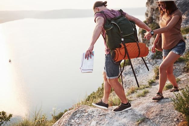 Два туриста с рюкзаками забираются на вершину горы и наслаждаются восходом солнца