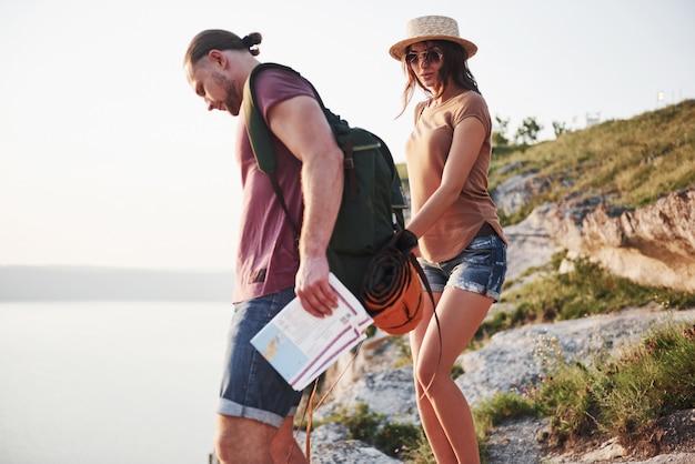 Два туриста с рюкзаками поднимаются на вершину горы и наслаждаются восходом солнца