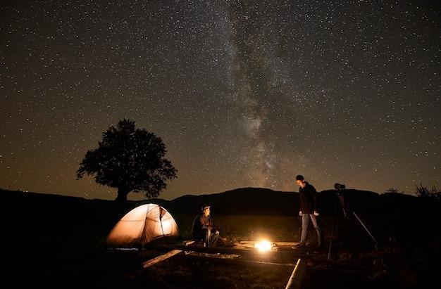 텐트 앞에서 모닥불을 피우고 있는 두 명의 관광객, 어두운 별이 빛나는 하늘 아래 삼각대에 있는 사진 카메라.