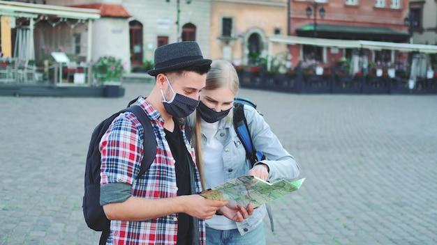 Два туриста в защитных масках проверяют карту на центральной площади города, затем любуются красивым местом. путешествуйте во время пандемии.