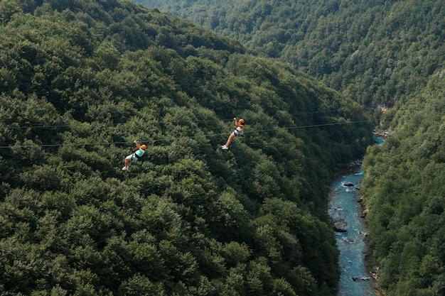 緑の山々と川を背景にジップラインで2人の観光客