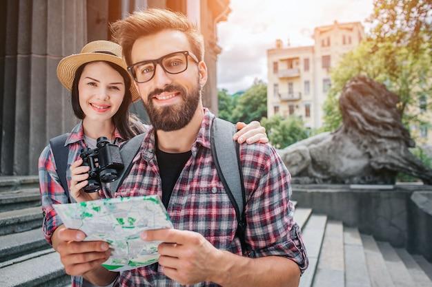 Два туриста стоят рядом со ступеньками снаружи. они смотрят на камеру и улыбаются. бородатый мужчина держит карту в руке. они веселые. женщина держит бинокль.