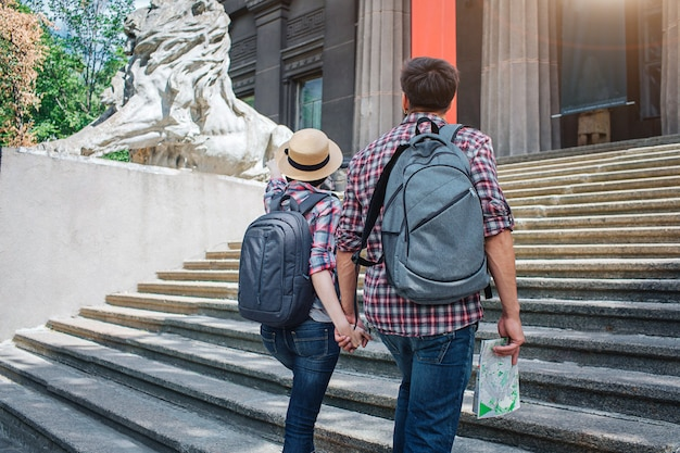 Two tourists walk up on steps and hold each other's hand. they look forward. he has map in hand. both have rocksacks on back.